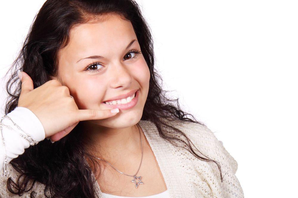 電話をするジェスチャーをする女性の写真